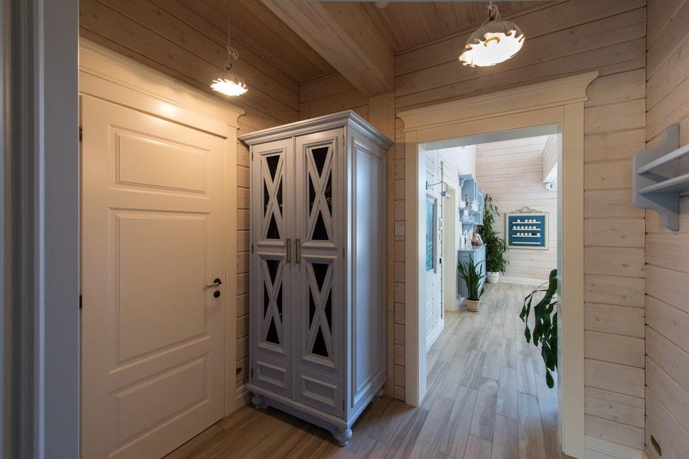 Узкий шкаф в прихожей деревянного дома