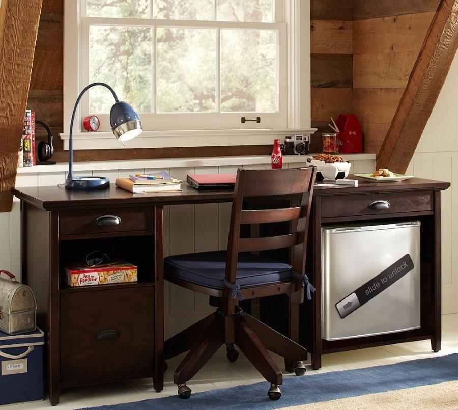 Деревянный стол перед окном комнаты подростка