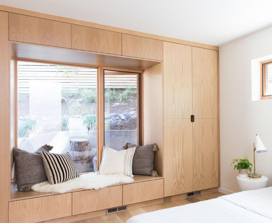 Шкафы вокруг окна в спальной комнате