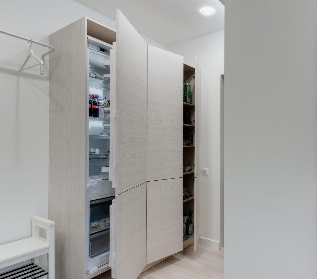 Приоткрытые дверцы на холодильнике в белом коридоре