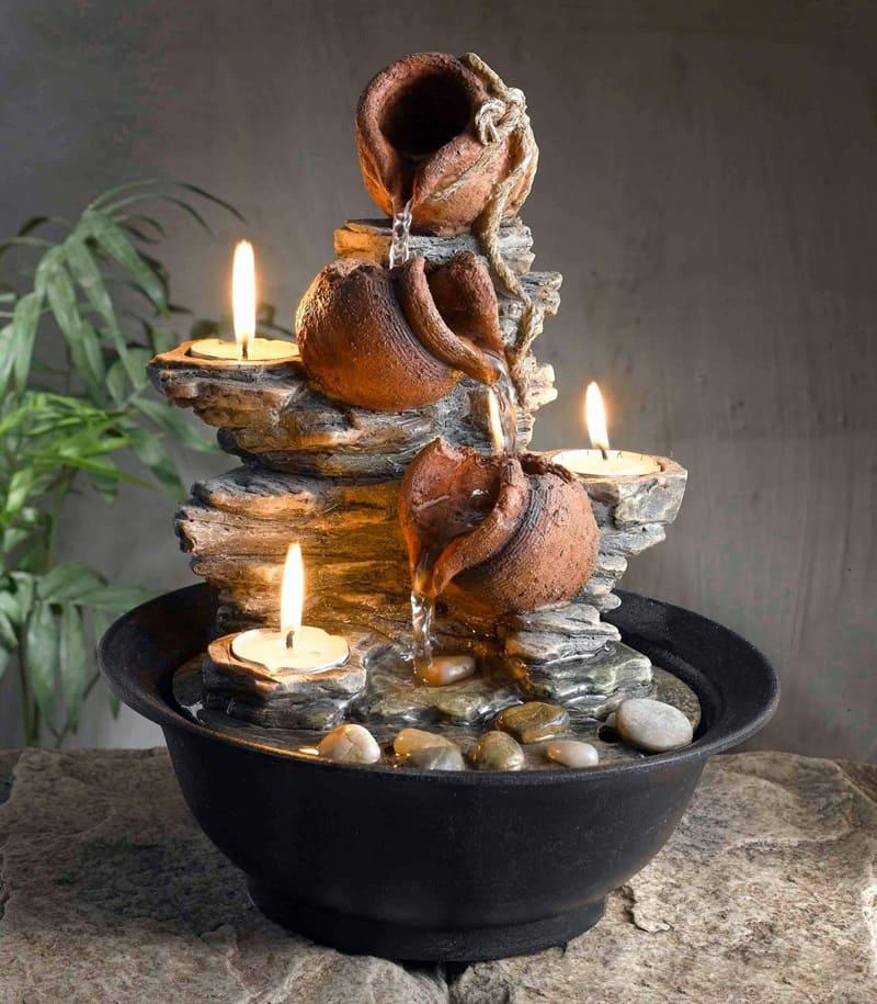 Декоративный каменный фонтан со свечами