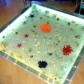 Квадратный аквариум на полу гостиной