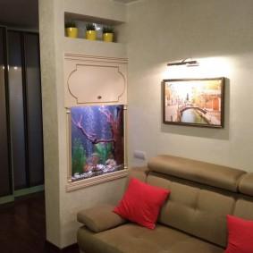 Небольшой аквариум в стене около дивана
