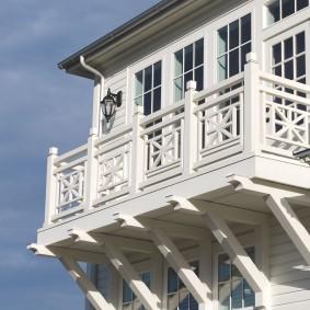 Белый балкон на фасаде деревянного дома