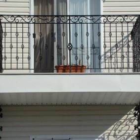 Балкончик небольшого размера с металлическими перилами