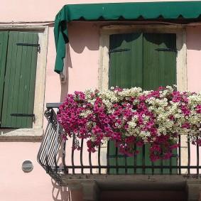 Красивый балкон с цветами на перилах