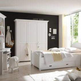 Белый шкаф на фоне темной стены