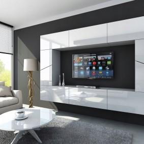 Белая мебель на серой стене зала