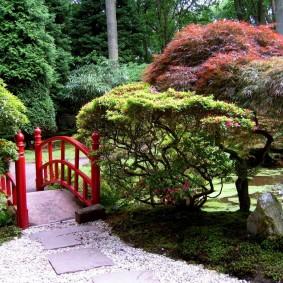 Мостик с красными перилами через садовый ручей