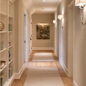 Светлые коврики на деревянном полу коридора