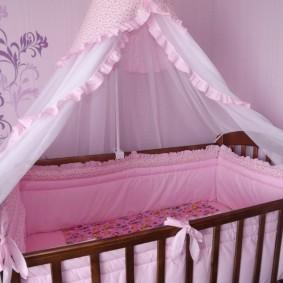 Розовая обивка стенок детской кроватки