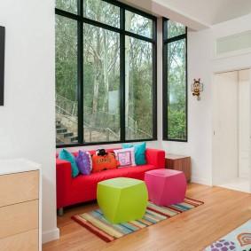 Красный диванчик перед большим окном