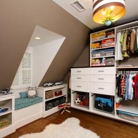 Детские вещи в гардеробе мансардной комнаты