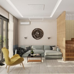 Просторный холл с диваном на первом этаже двухуровневой квартиры