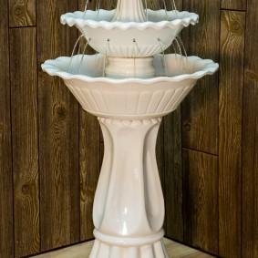 Белый комнатный фонтан в углу спальни