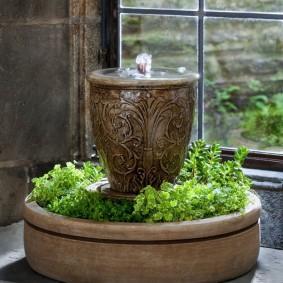 Декоративный фонтан с живыми растениями на подоконнике квартиры