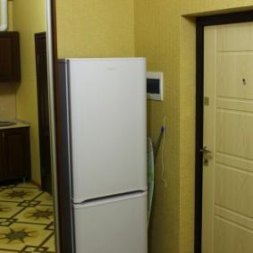 Холодильник около входной двери в двухкомнатной квартире