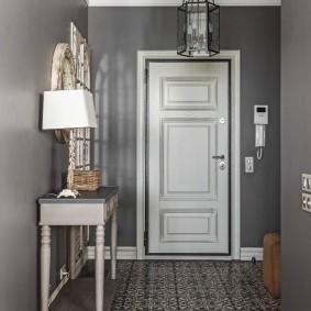 Белая дверь в коридоре с серыми стенами