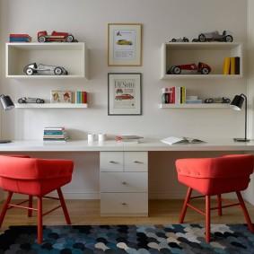 Красные стулья перед письменным столом