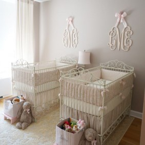 Коробки с детскими игрушками перед небольшими кроватками