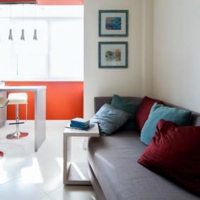 Серый диван вдоль белой стены кухни