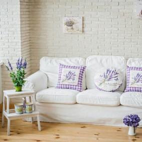Белый диван у стены гостиной комнаты