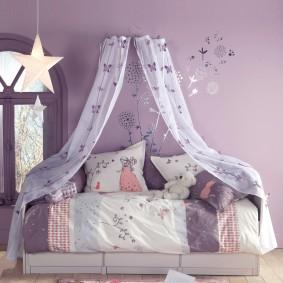Детская кровать возле сиреневой стены