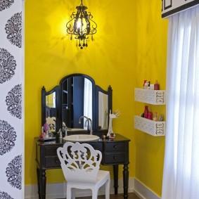Черное трюмо на фоне желтой стены