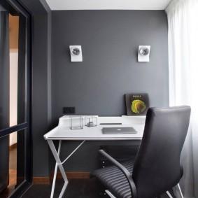 Белый столик около серой стены