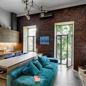 Синий диван в комнате с кирпичной стеной