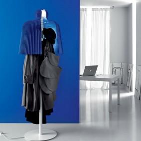 Вешалка для одежды на фоне синей стены