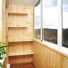 Небольшие полочки на деревянной стене балкона