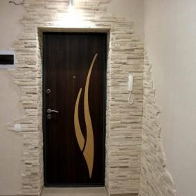 Декор камнем пространства над входной дверью