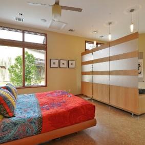 Широкая кровать с пестрым текстилем