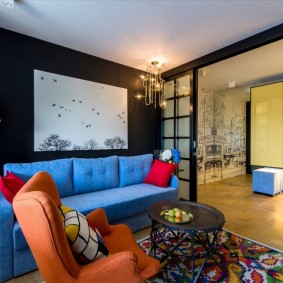 Красные подушки на синем диване