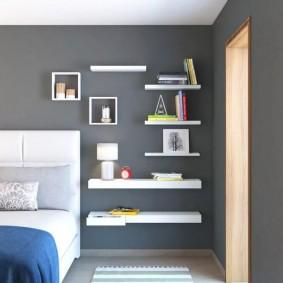 Белые полки на серой стене спальни