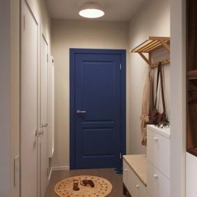 Синяя дверь в прихожей с белыми стенами