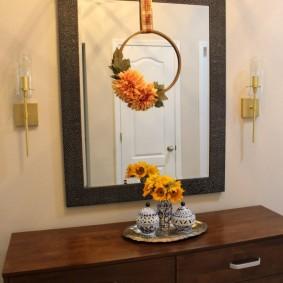 Комод коричневого цвета под зеркалом в коридоре