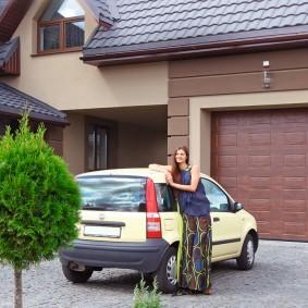 Малолитражный автомобиль перед воротами гаража