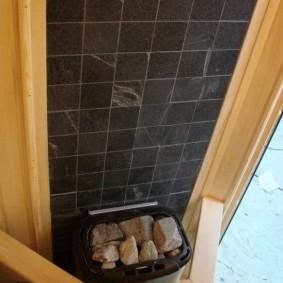 Керамическая отделка стены на печкой в бане