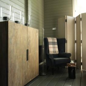 Мягкое кресло в комнате дома из бруса