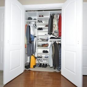 Желтый пылесос в шкафу с распашными дверками