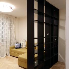 Угловой диван за черным стеллажом
