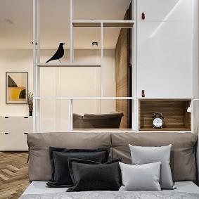Декоративные подушки на кровати в спальной зоне квартиры