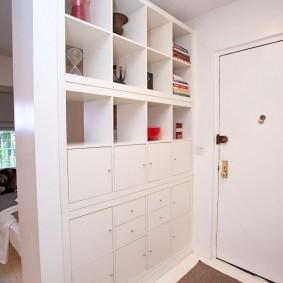 Белый стеллаж в прихожей комнате