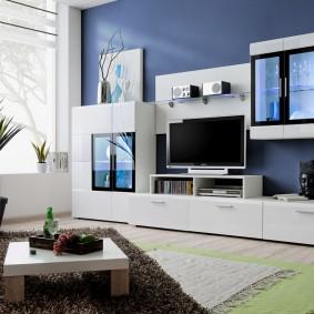 Белая стенка на фоне синей стены гостиной