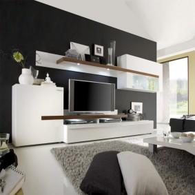 Белая корпусная мебель около черной стены