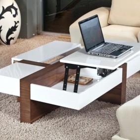 ноутбук на столике-трансформере в гостиной комнате