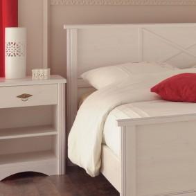 Красная подушка на белой кровати