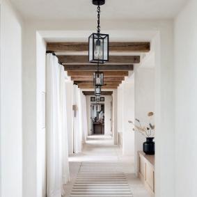 Поперечные балки на потолке белого коридора